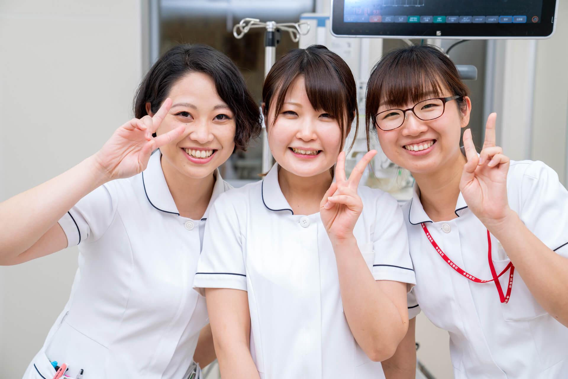 写真:看護師が三人並んでピースしている