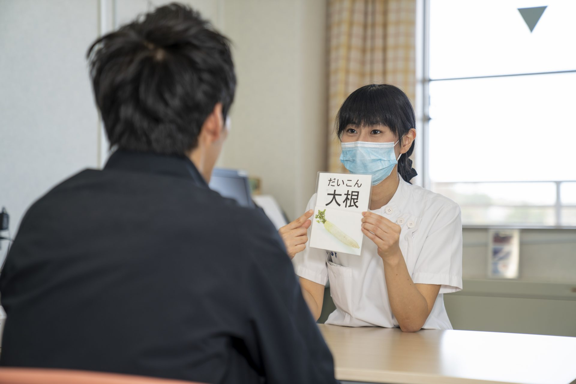 写真:言語聴覚士が患者にカードを見せている様子2