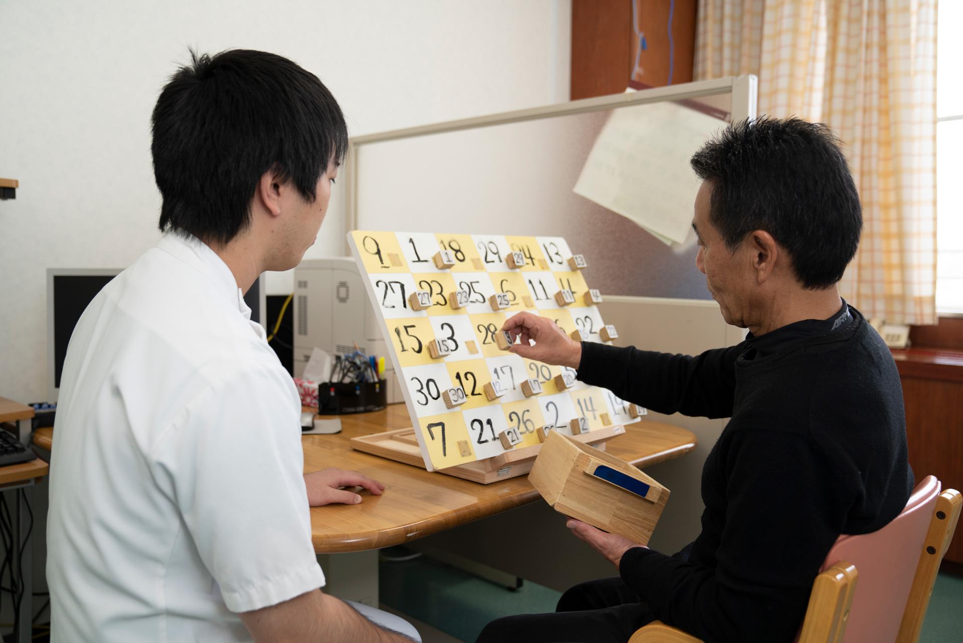 写真:作業療法士と患者の後ろ姿