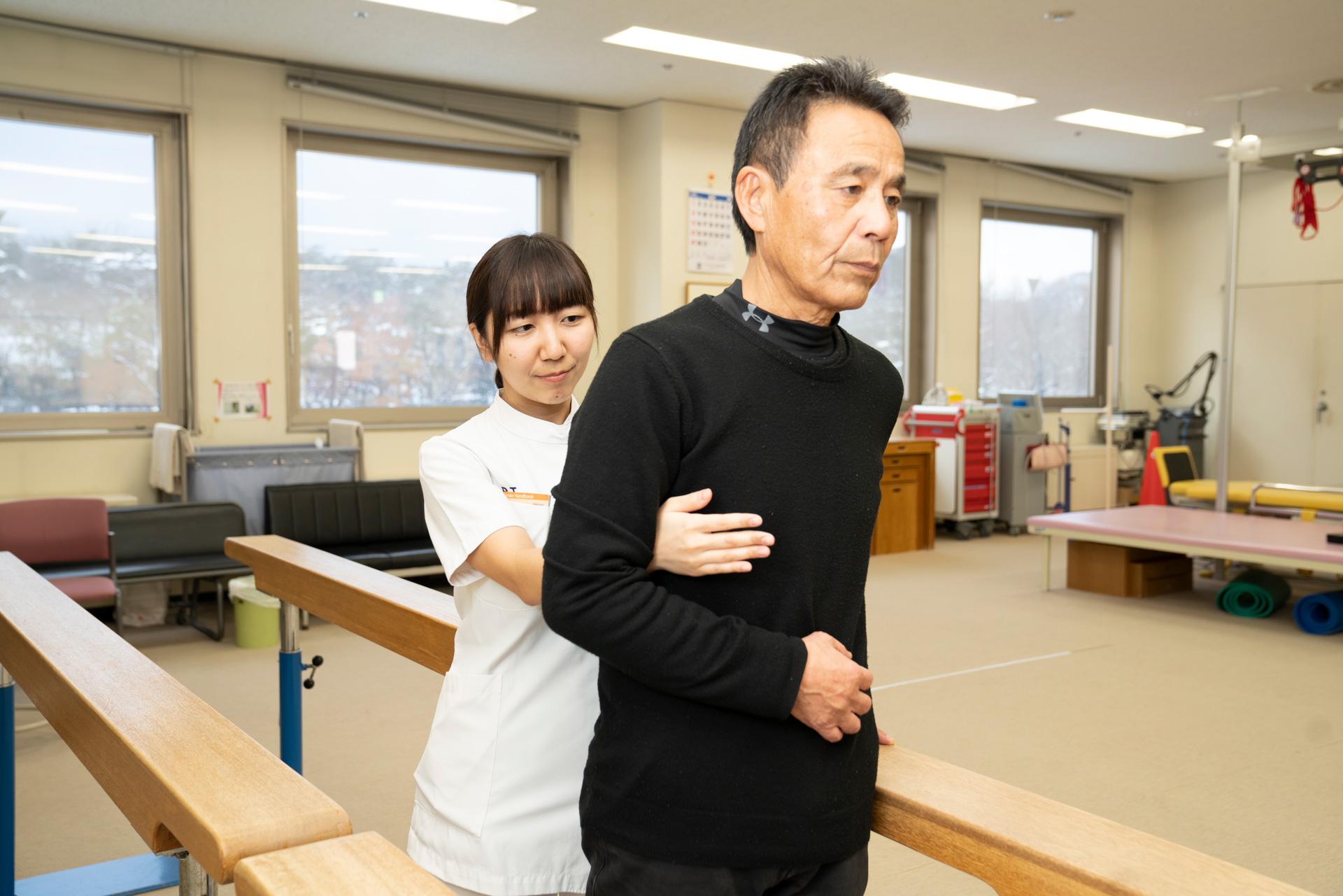 写真:理学療法士が患者の歩行の補助をしている様子