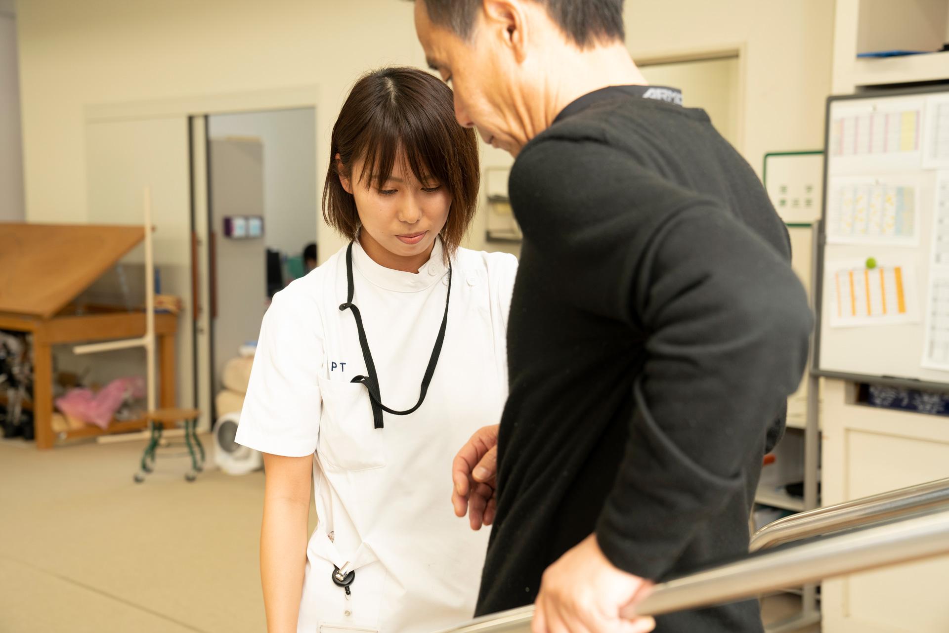写真:理学療法士が患者が階段を降りる補助をしている様子