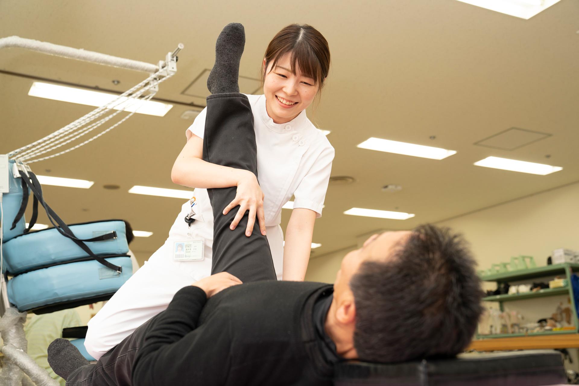 写真:理学療法士が患者の足を上げている様子