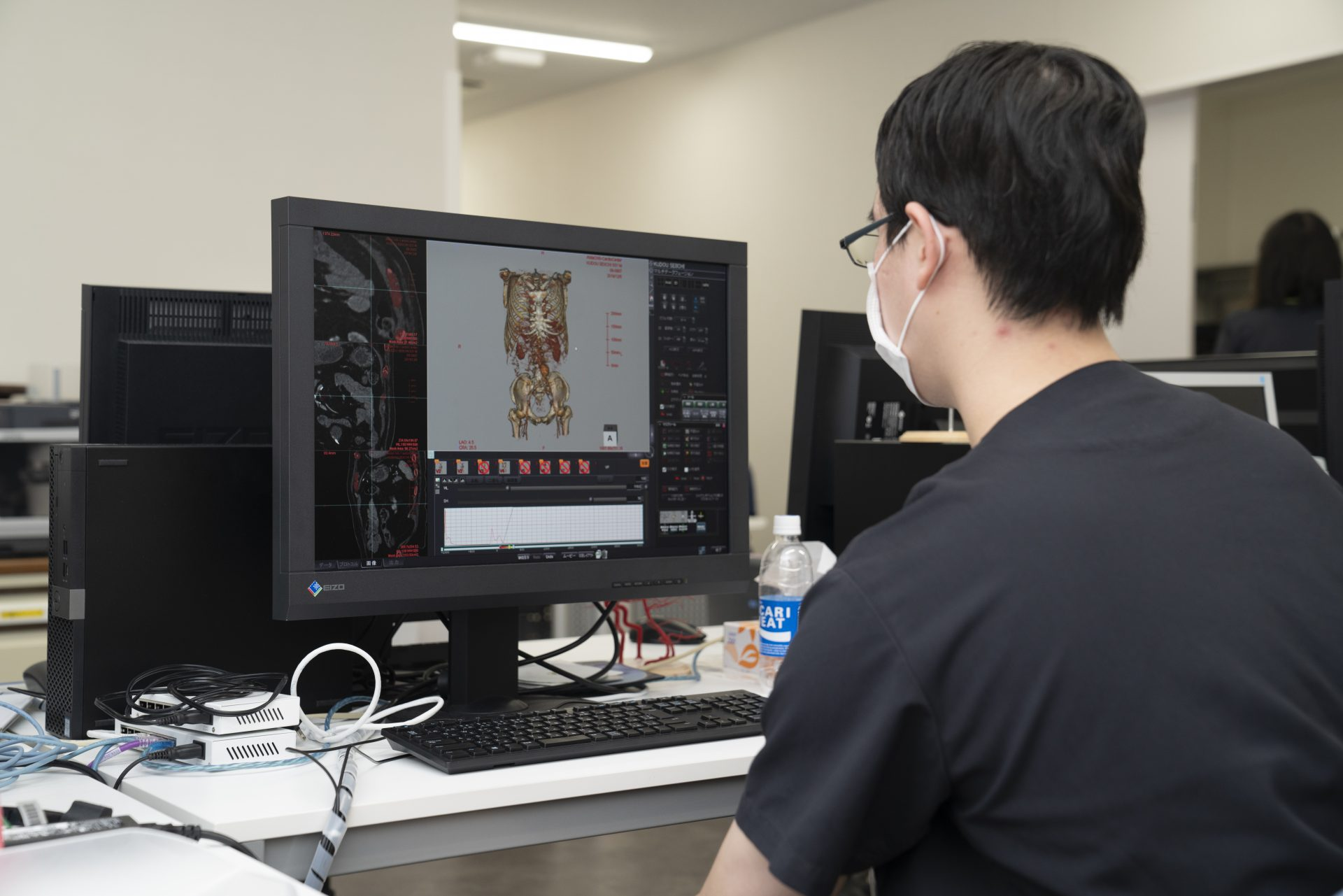 写真:診療放射線技師がパソコンを見ている後ろ姿