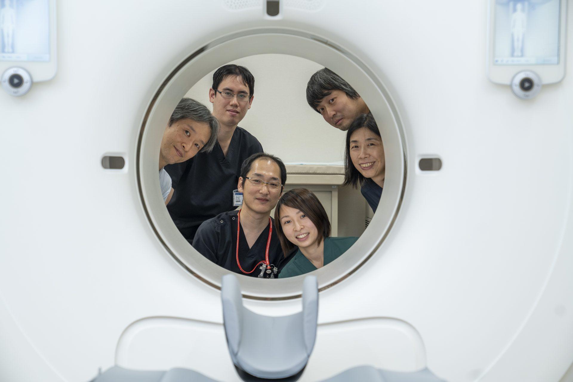 写真:診療放射線技師がCTの向こうから顔を出している様子
