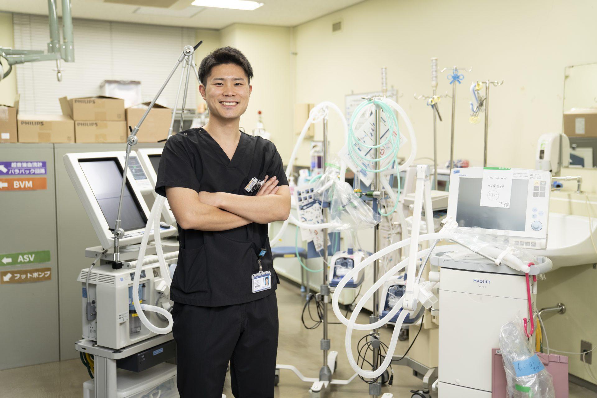 写真:臨床工学技士が笑顔で機会の前に立っている