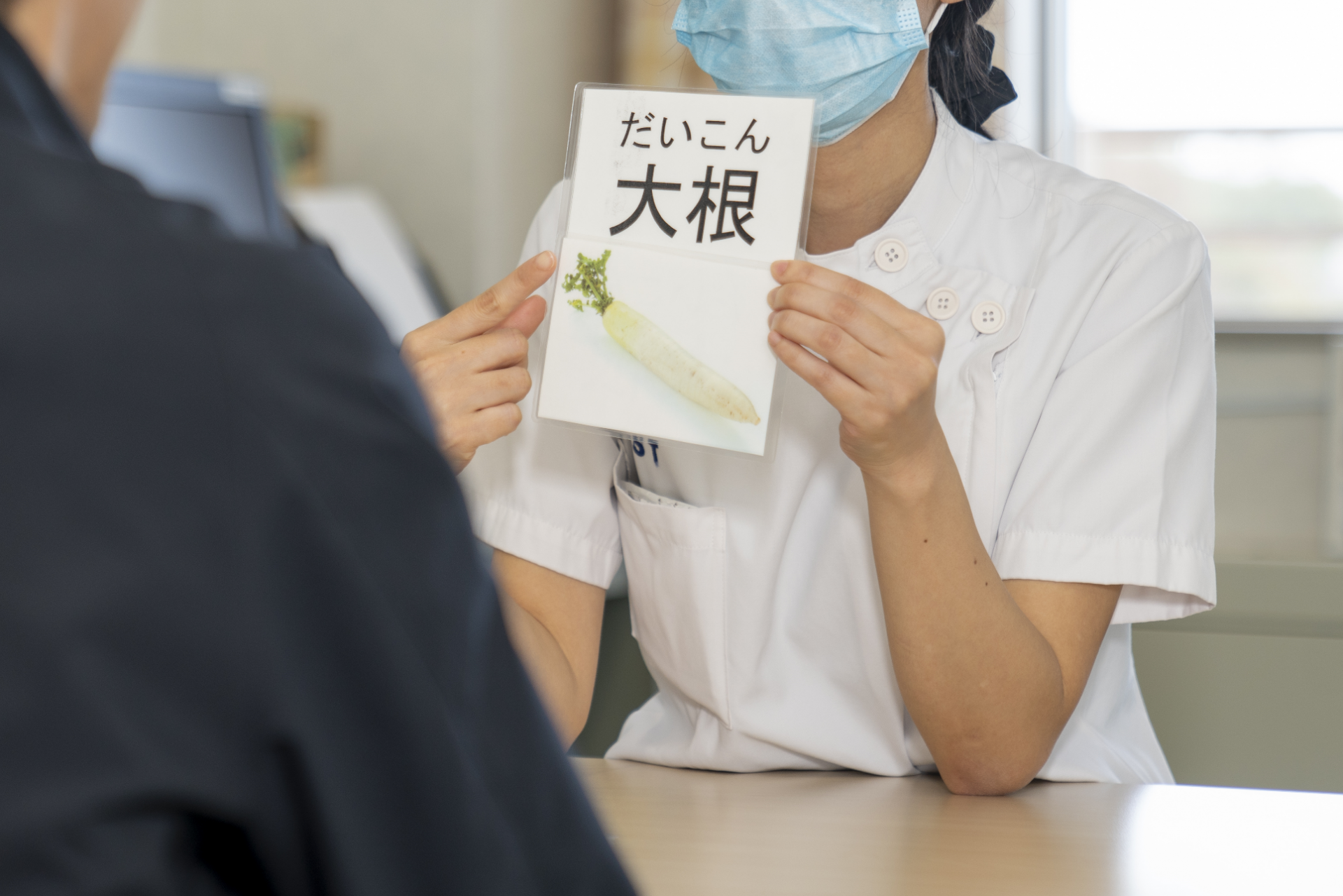 写真:言語聴覚士が患者にカードを見せている様子1