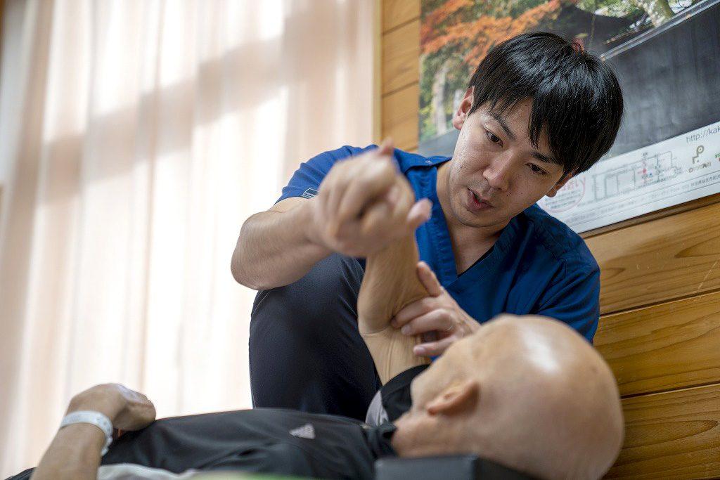 写真:作業療法士が患者さんの補助をしている